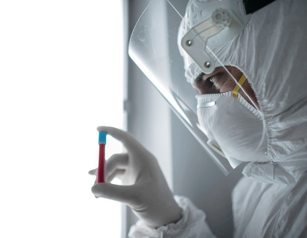 in a chemistry lab, a male researcher holds a tube with the coronavirus virus (Foto: Getty Images)