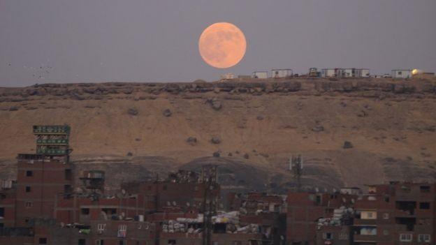 No Cairo, no Egito, o laranja da lua contrastou com a cor da areia (Foto: EMAD KARIM/BBC)