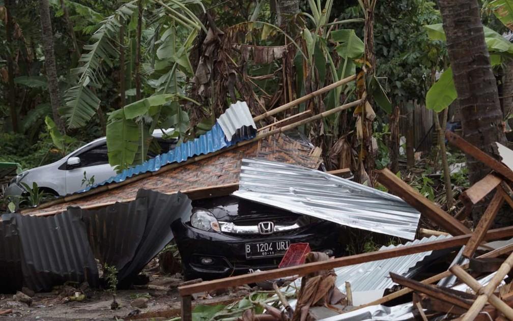 Carro coberto por destroços em área devastada na Indonésia — Foto: Dian Triyuli Handoko/ AP Photo