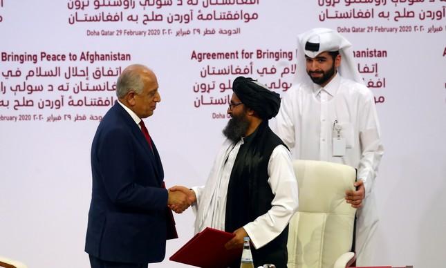 Mulá Abdul Ghani Baradar, representante do Talibã, e Zalmay Khalilzad, enviado dos EUA, após assinatura de acordo