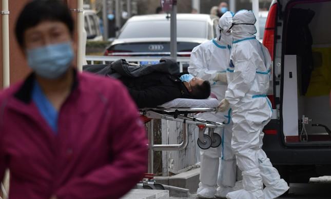 Profissionais de saúde fazem a transferência de paciente com Covid-19 em Pequim, na China