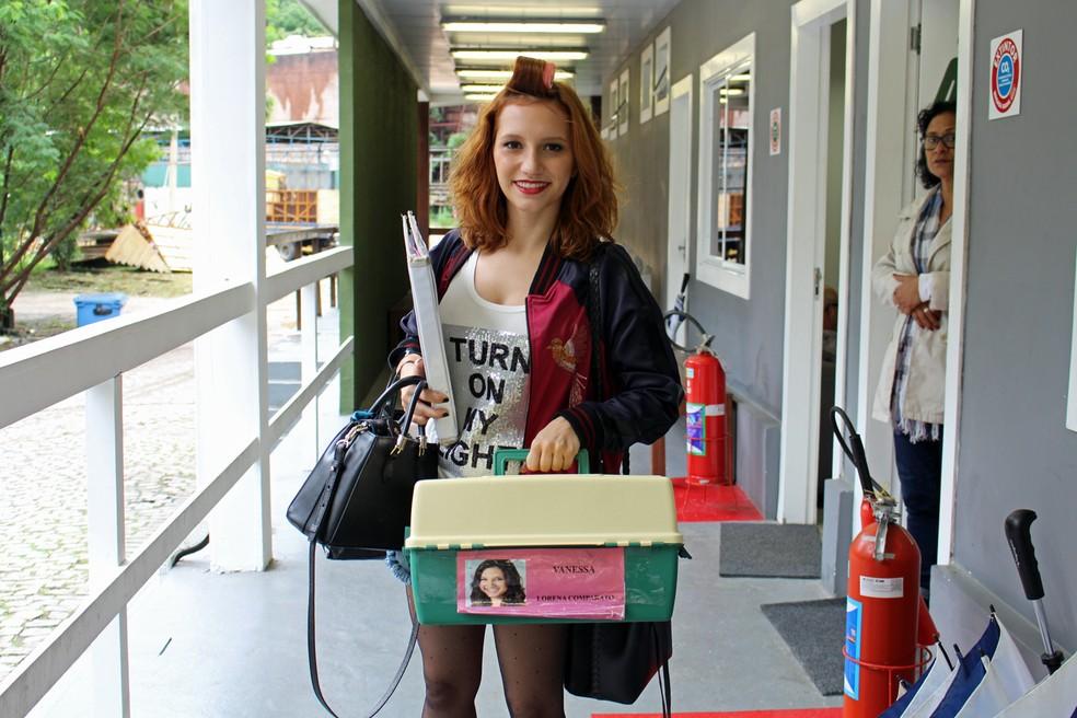 Lorena Comparato chega para gravar na cidade cenográfica com a malinha de acessórios de sua personagem Vanessa (Foto: TV Globo)