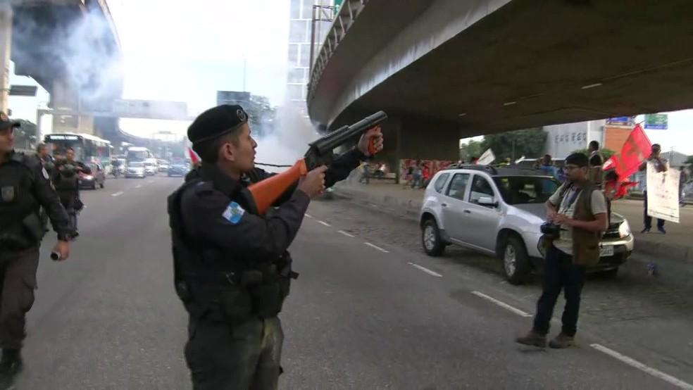 Rio de Janeiro, 7h37: PM saca arma não letal próximo a manifestantes em local onde foi jogada bomba de efeito moral — Foto: Reprodução/TV Globo