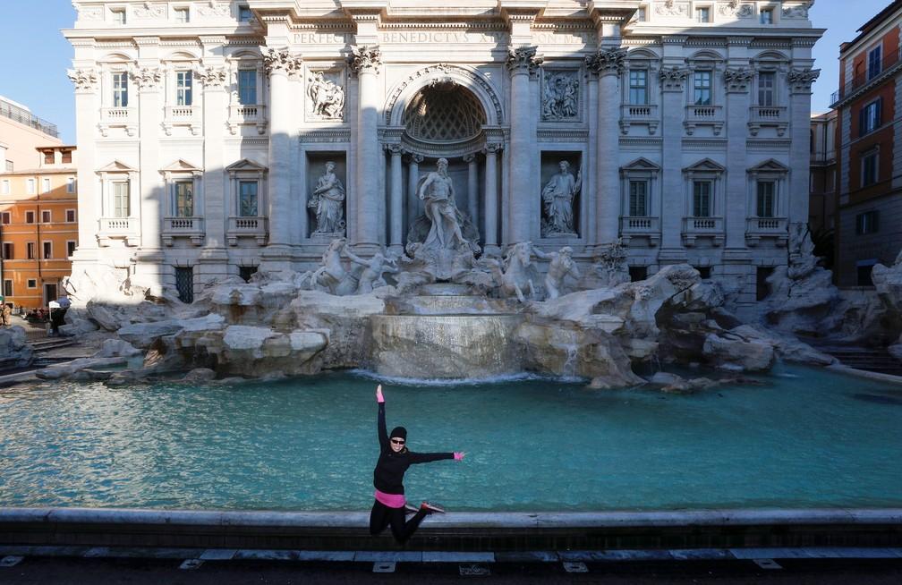 Mulher tira foto sozinha na Fontana di Trevi, em Roma, um local geralmente lotado de turistas, e que agora está vazio por causa da restrição de deslocamento imposta pelo governo — Foto: Reuters/Guglielmo Mangiapane