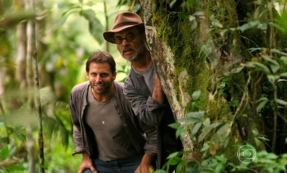 Cassiano (Henri Castelli) e Duque (Jean Pierre Noher) usam a floresta como rota de fuga, em 'Flor do Caribe' — Foto: Globo