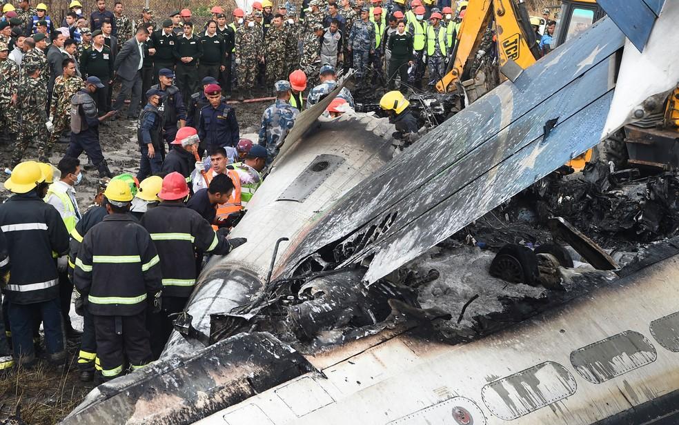 -  Funcionários trabalham entre os destroços do avião da US-Bangla Airlines que caiu no aeroporto de Katmandu, no Nepal, na segunda-feira  12   Foto: Pr