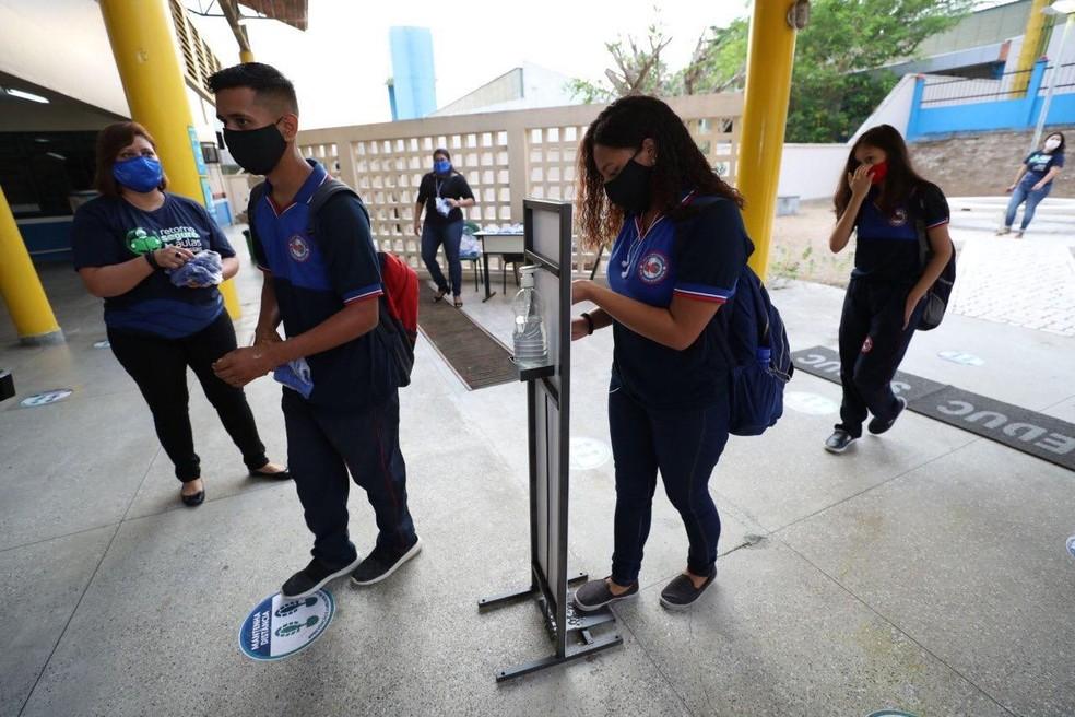 Alunos têm que higienizar mãos e passar por aferição de temperatura antes de entrar nas escolas. — Foto: Divulgação/Secom