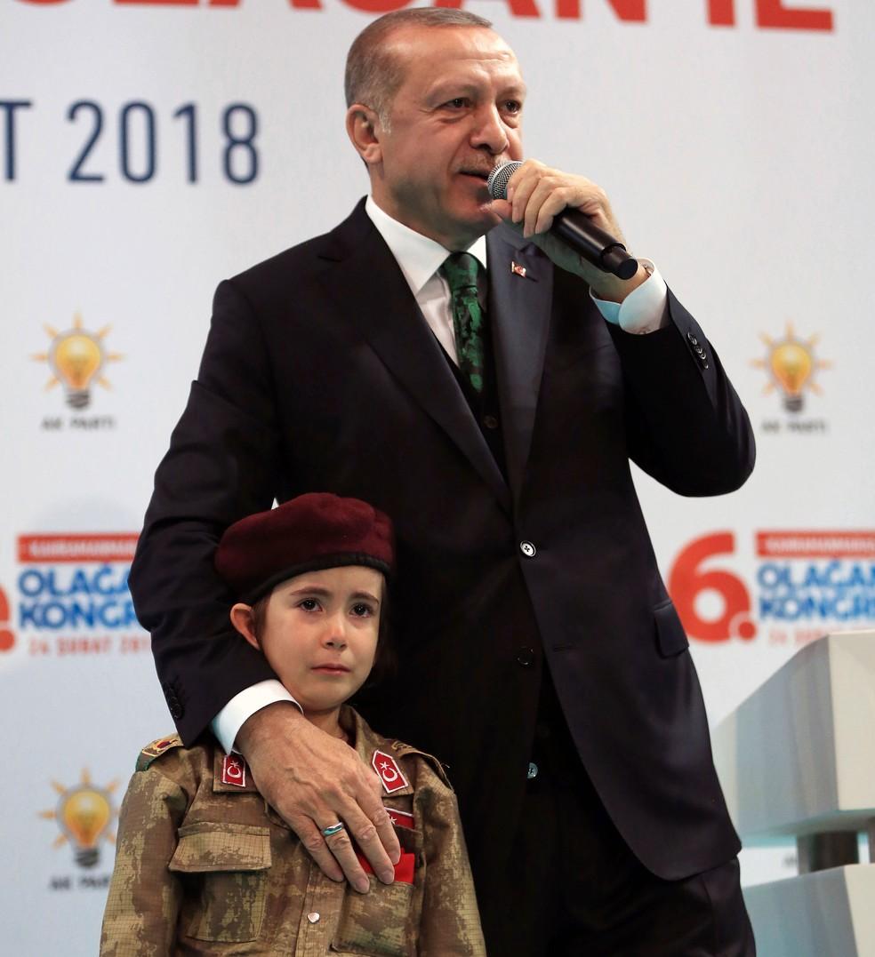 O presidente da Turquia, Recep Tayyip Erdogan, posa ao lado da menina Amine Tiras, de 6 anos, durante congresso de seu partido na cidade de Kahramanmaras, no sábado (24) (Foto: Murat Cetinmuhurdar/Pool Photo via AP)