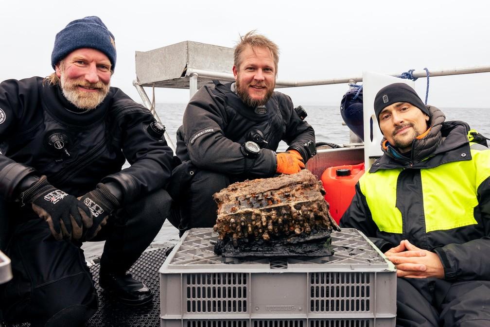 Mergulhaores Christian Howe, Florian Huber e Uli Kunz com equipamento nazista encontrado no mar Báltico — Foto: Christian Howe/Reuters
