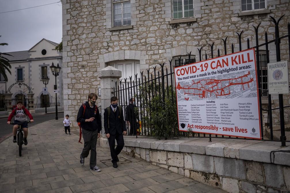 Alunos passam diante de cartaz com informação sobre a Covid-19 em Gibraltar, em foto de 4 de março de 2021 — Foto: Bernat Armangué/AP Photo
