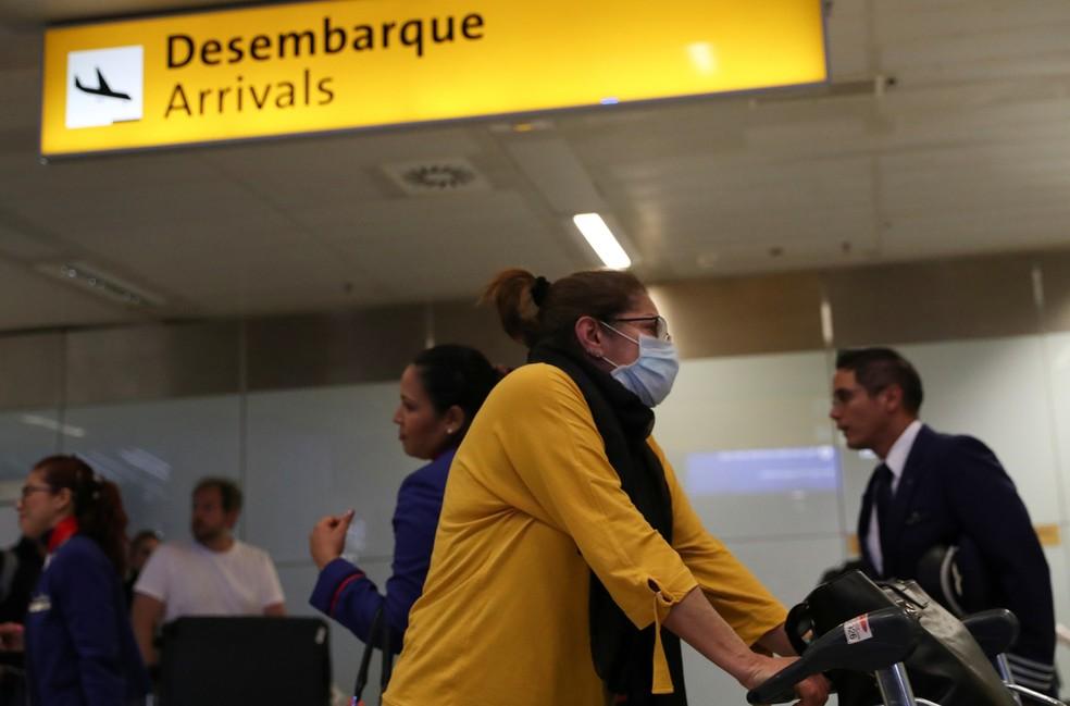 Mulher com mascara em aeroporto