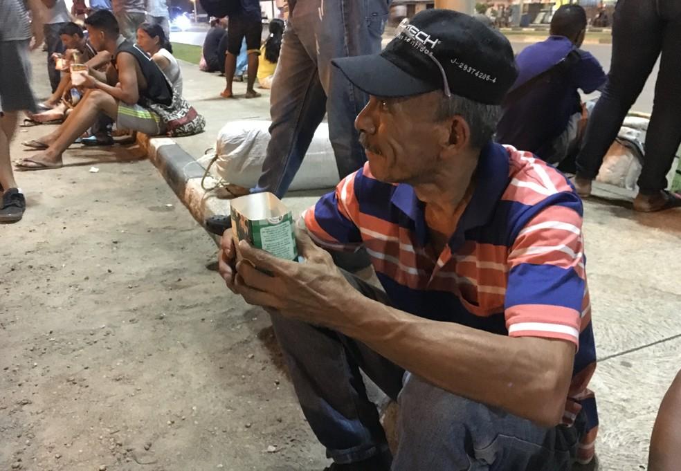 Carlos Salas, 43, toma sopa em uma embalagem de leite reaproveitada — Foto: Emily Costa/G1 RR