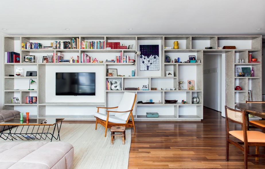 A estante que abriga a televisão neste living foi desenhada pelo arquiteto Felipe Hess, responsável pelo projeto. Toda feita com nichos de concreto moldado e com recuo no piso e no teto, o efeito é de uma caixa solta e cheia de leveza