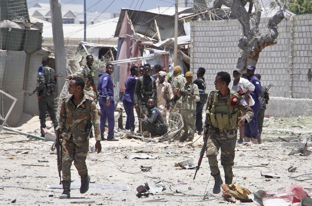 Soldados somalianos rondam local do ataque de carros-bomba em Mogadício, Somália, neste sábado (23). — Foto: AP/Farah Abdi Warsameh