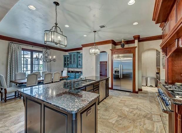 A cozinha americana é de inox com madeira (Foto: Christie's International Real Estate/ Reprodução)