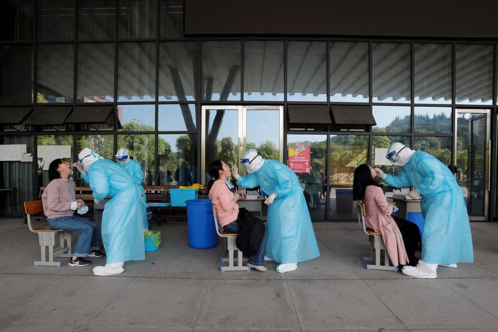 27 de abril - Médicos de um hospital coletam amostras de professores do ensino médio para testes em uma escola após o surto da doença por coronavírus em Yichang, província de Hubei, na China — Foto: China Daily via Reuters