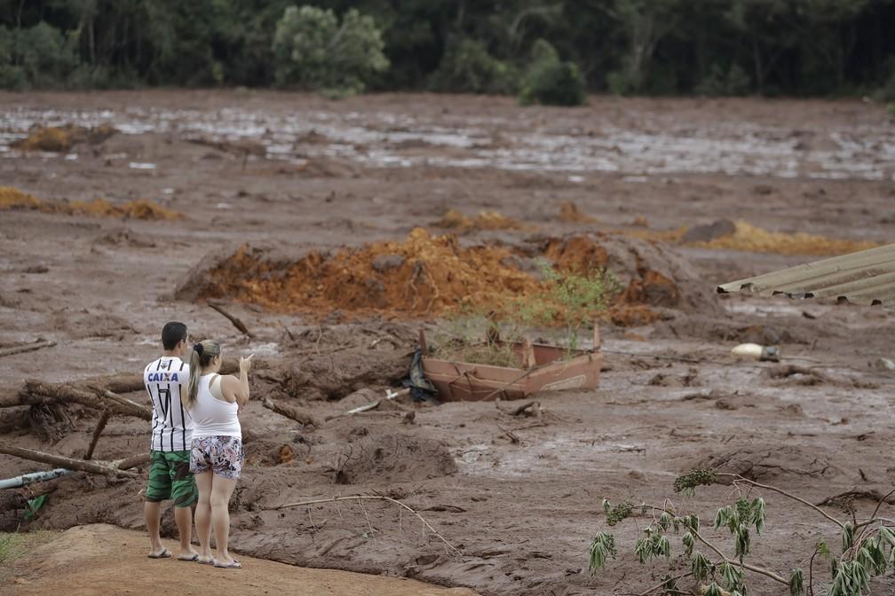 Casal com familiares desaparecidos observa a área inundada após o rompimento da barragem da Vale em Brumadinho.