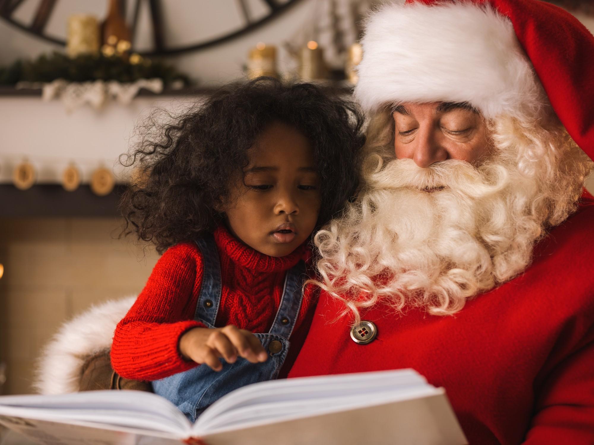 Menina lendo livro no colo do Papai noel (Foto: Thinkstock)