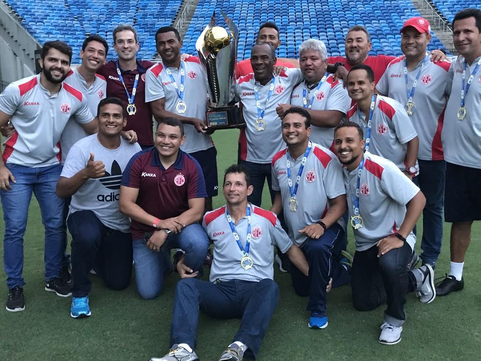 ... André Luiz (sentado ao centro) comemorou o título com a comissão  técnica do América 0bc7a1b24d2fc