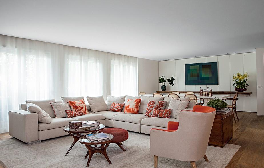 O estar neutro abre-se a pitadas de laranja, seja nas almofadas sobre o sofá italiano, seja no tecido da poltrona. A cor quente combina com o bege. Projeto da designer de interiores Renata Paula