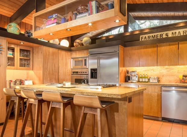 A madeira também está presente na cozinha que possui superfícies de granito (Foto: Shawn Bishop Photography/ Reprodução)