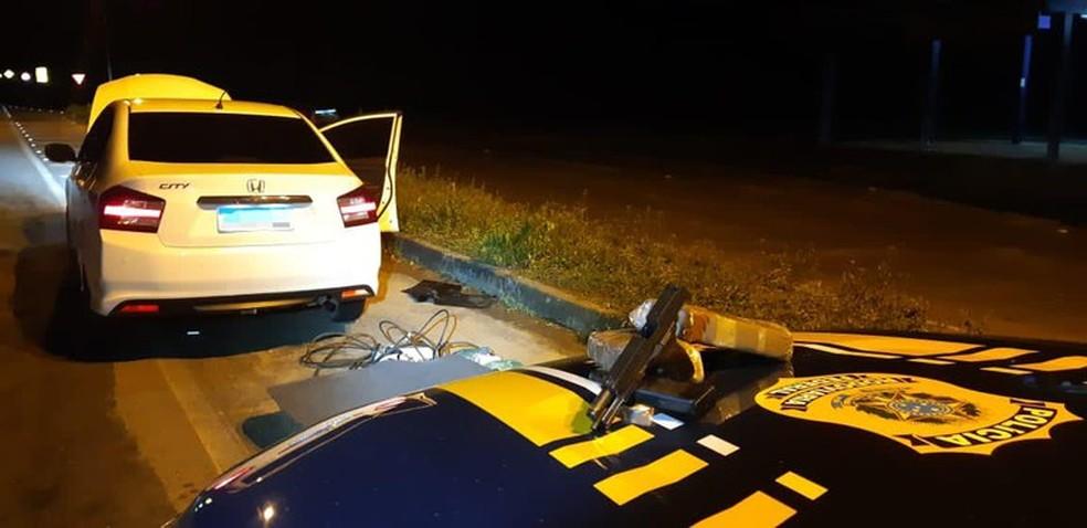 Arma e drogas estavam escondidas em um fundo falso no painel do carro — Foto: Divulgação/PRF