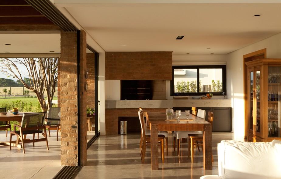 A sala de jantar desta casa foi integrada à área da churrasqueira, com mesa e cadeiras da Antigo Armazém e balcão de granito da Irmãos Tomazelli. Projeto do escritório de arquitetura Zeferin