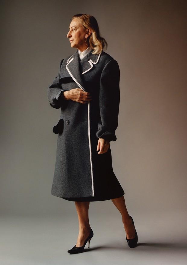 Feature on Prada, Miucca Prada's luxury fashion label through the decades, Portrait of designer Muicca Prada wearing white shirt underneath grey tailored coat with white trim and black court shoes (Foto: Jamie Hawkesworth)