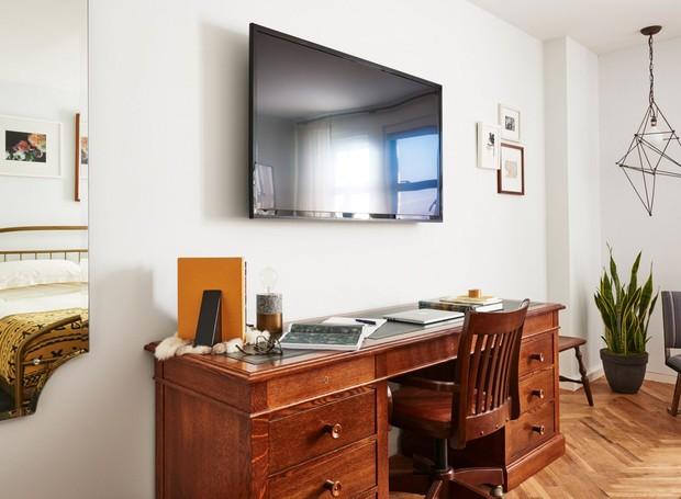 Na foto, o lustre de metal ao fundo se opõe à madeira escura da escrivaninha (Foto: Deezen/ Reprodução)