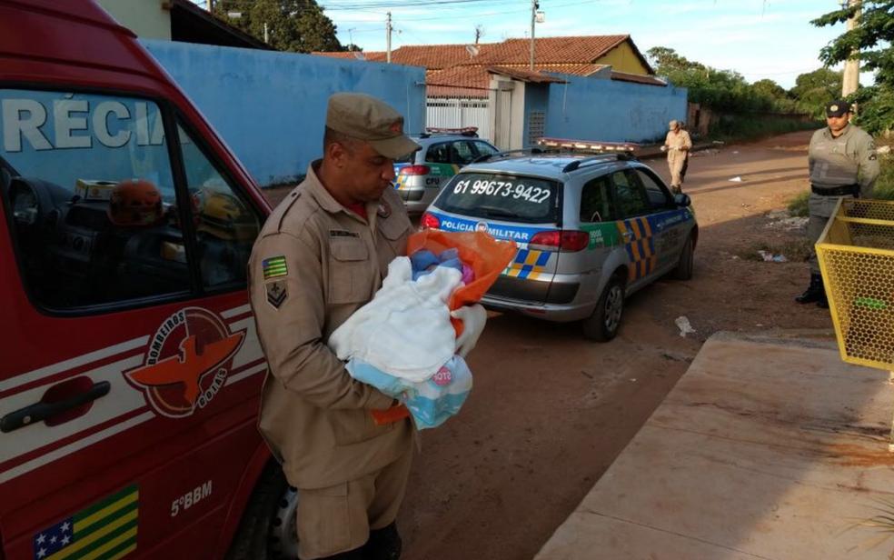Bombeiro segura bebê achado em lata de lixo em Valparaíso de Goiás nesta terça-feira (13) (Foto: TV Anhanguera/Reprodução)