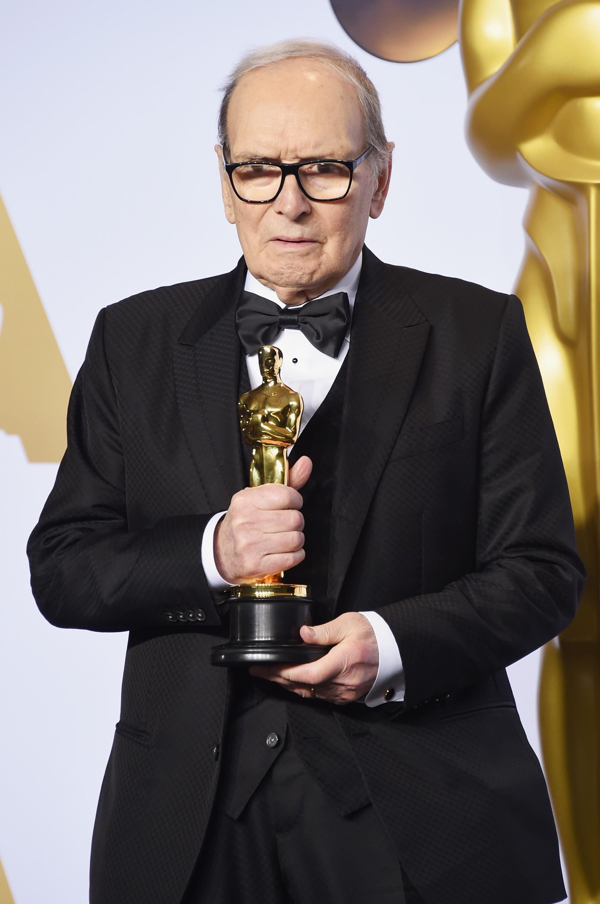 O compositor Ennio Morricone com o Oscar vencido por ele pela trilha sonora de Os Oito Odiados (2015) (Foto: Getty Images)