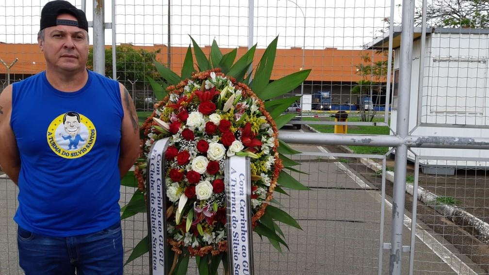 Djalma Schiavi levou uma coroa de flores para o Aeroporto Internacional de Viracopos, em Campinas, onde o corpo do apresentador Gugu desembarcou — Foto: Eduardo Rodrigues/EPTV