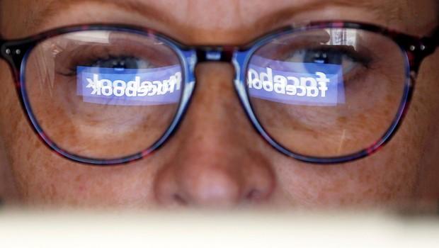 Logotipo do Facebook é refletido nos óculos de uma mulher - internet - redes sociais (Foto: Regis Duvignau/Reuters)