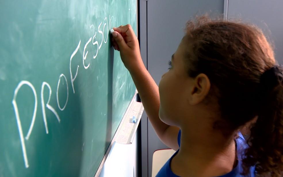 Aluna escola a palavra 'professora' na lousa. Docentes não recebem formação adequada para usar tecnologias na educação. — Foto: Reprodução EPTV