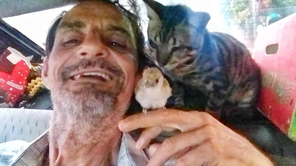 Luiz no carro onde vive com Miau, e o passarinho que também morava com eles: 'Amor pelos animais' — Foto: Arquivo pessoal