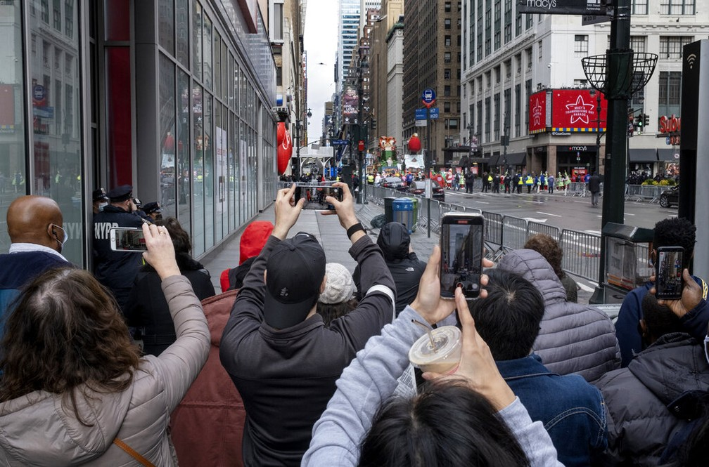 De longe, pessoas tentam acompanhar um pouco do desfile do Dia de Ação de Graças em Nova York nesta quinta-feira (26) — Foto: Craig Ruttle/AP Photo