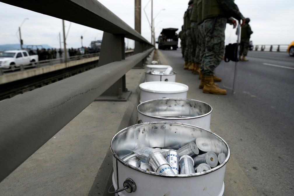 Policiais fazem guarda perto de latas de gás lacrimogêneo na Ponte da Unidade Nacional em Durán, no Equador, nesta terça (8) — Foto: Reuters/Santiago Arcos