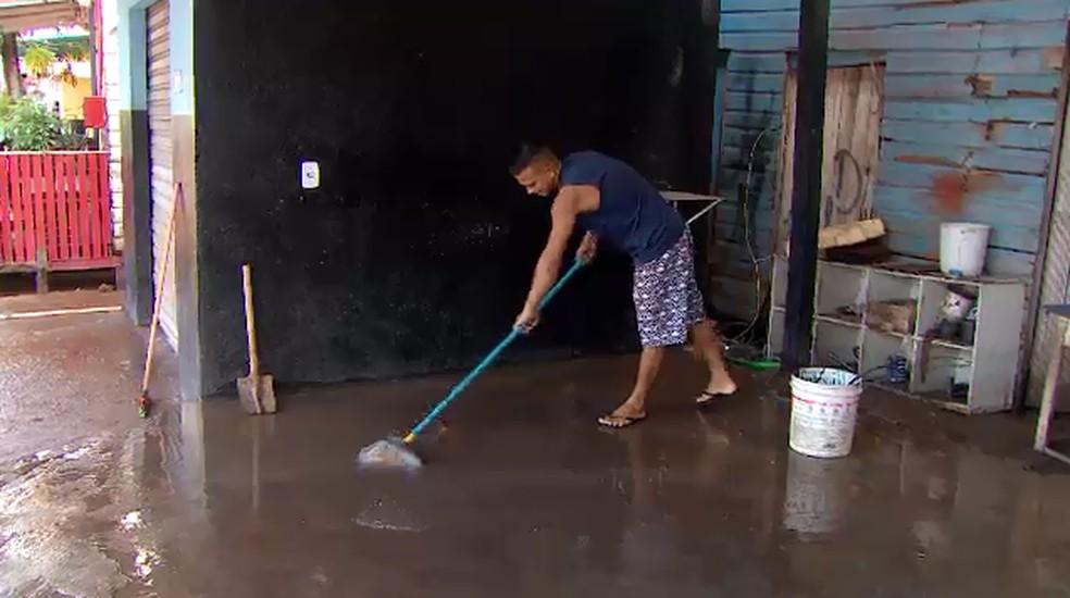 Morador limpa frente de casa após forte chuva em Macapá — Foto: Rede Amazônica/Reprodução