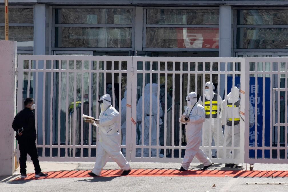 Trabalhadores vestindo macacões protetores são vistos em um centro de exposições convertido em um local para examinar chegadas do exterior em Pequim, na China, neste domingo (15). Quem chegar do exterior ao país será transferido e ficará por 14 dias nas instalações para quarentena  — Foto: Ng Han Guan/AP
