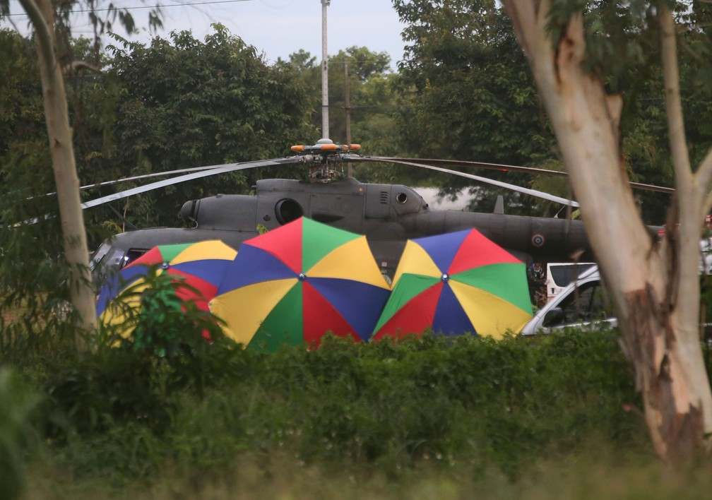 Polícia protege com guarda-chuvas saída de resgatado em caverna na Tailândia, na terça-feira (10) (Foto: Sakchai Lalit/ AP)