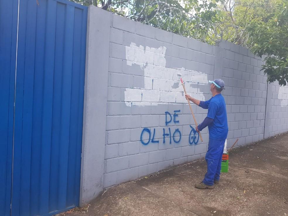 Funcionários tentam limpar muros da Toca da Raposa que foram pichados — Foto: Diogo Finelli / Globoesporte.com