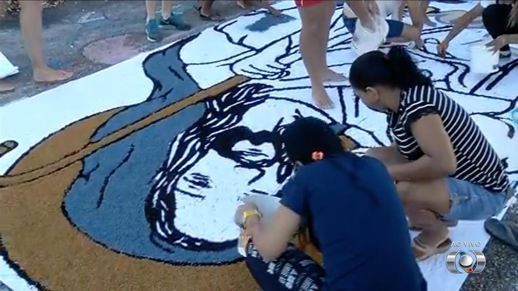 Em Palmas (TO), fiéis confeccionam tapete do estacionamento da Catedral (Foto: TV Anhanguera/Reprodução)