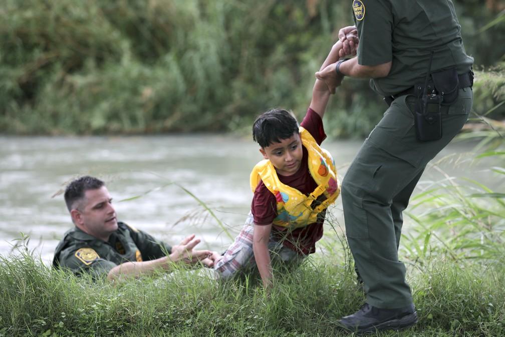 Menino hondurenho de 7 anos é resgatado por agentes de fronteira americanos no Rio Grande, na fronteira entre Estados Unidos e México, no dia 10 de maio. — Foto: Bob Owen/The San Antonio Express-News via AP