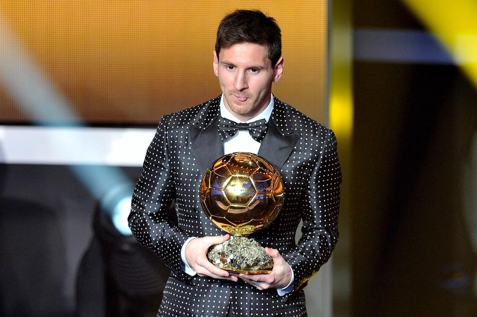 Lionel Messi, com seu icônico terno de bolinhas, e a Bola de Ouro de 2012 — Foto: Agência Getty Images
