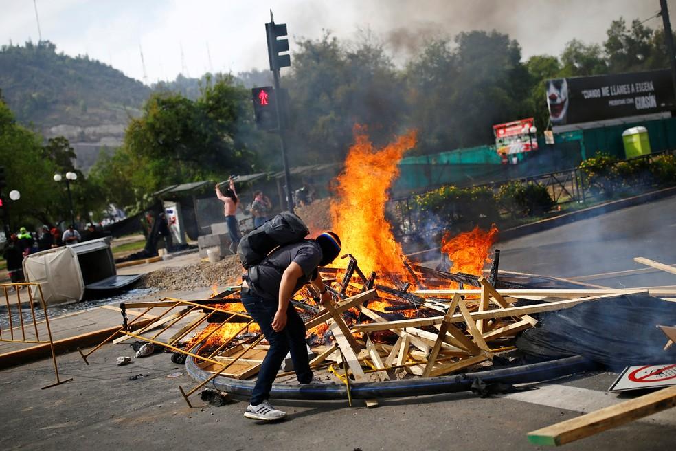 Manifestante acende uma barricada durante protesto contra o aumento da tarifa do metrô em Santiago do Chile — Foto: Edgard Garrido/Reuters