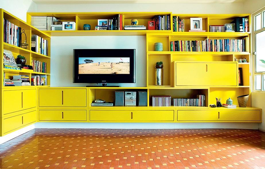 A arquiteta Cláudia Pecego projetou uma estante de MDF com acabamento em gofrato amarelo. Para amenizar o visual marcante, a profissional solicitou que a base da estante fosse pintada de branco, dando a impressão de que o móvel está suspenso