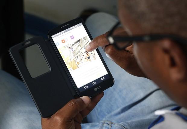 Homem lê notícias no celular ; smartphone ; mídia ;  (Foto: Cecília Bastos Ribeiro/USP Imagens)