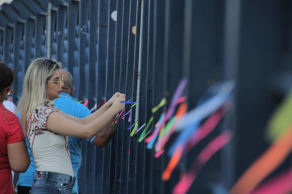 Devota amarra fita da Padoreira na passarela da fé (Foto: Carlos Santos/G1)