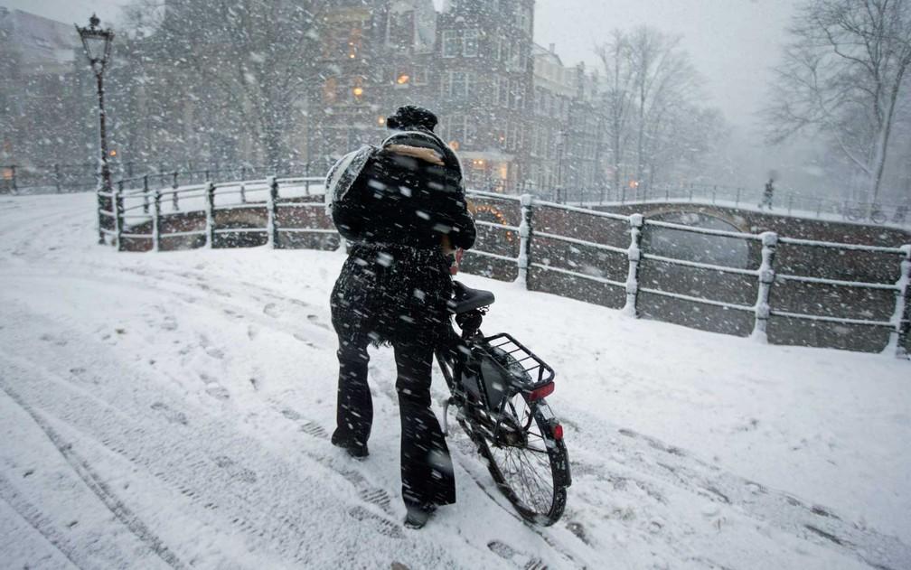 Uma mulher empurra sua bicicleta sobre a neve em Amsterdã, Holanda (Foto: Peter Dejong / AP Photo    )