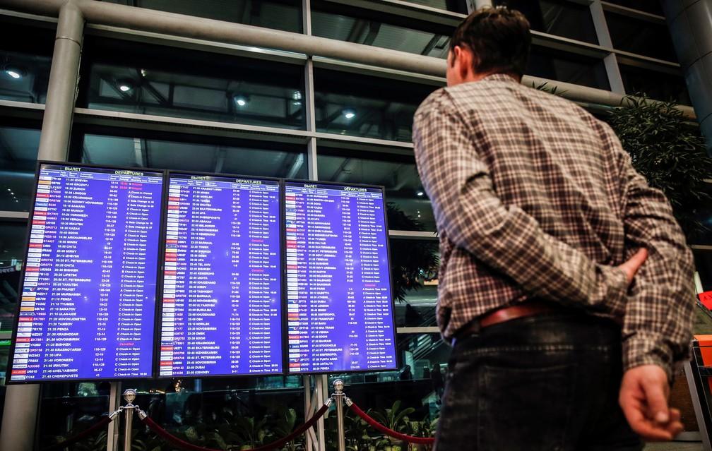 Homem olha tela com horários de voo no Aeroporto Internacional de Domodedovo, em Moscou, logo após avião que saiu do local cair nos arredores da capital russa  (Foto: Maxim Zmeyev/AFP)